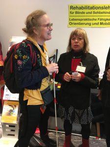 Debby in gesprek met mobiliteitstrainer van een revalidatiecentrum.
